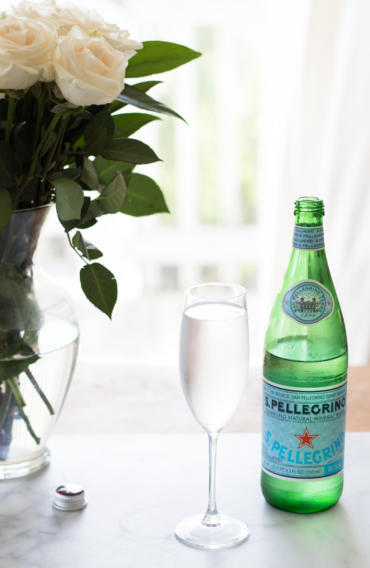 How to drink more water_Pellegrino, champ glass, and white roses_joyfetti.com